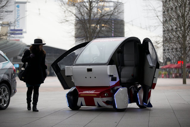 A woman poses for photographers beside a prototype driverless car called a LUTZ (Low-carbon Urban Transport Zone) Pathfinder Pod during a launch event for the media near the O2 Arena in London, Wednesday, February 11, 2015. (Photo by Matt Dunham/AP Photo)