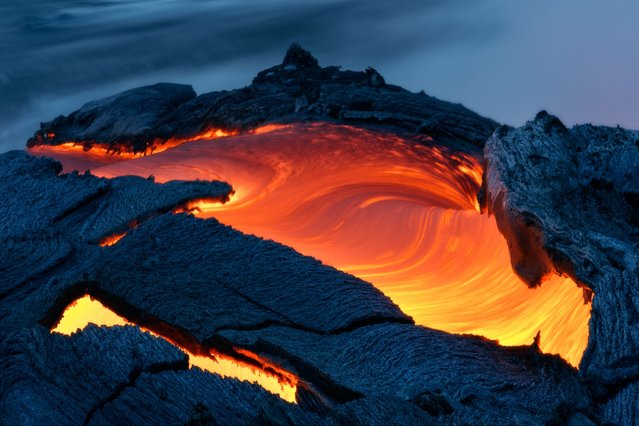 Lava flow from the Kilauea Volcano enters the sea south of Kalapana in Big Island, Hawaii, on August 26, 2013. (Photo by Miles Morgan/Barcroft Media)
