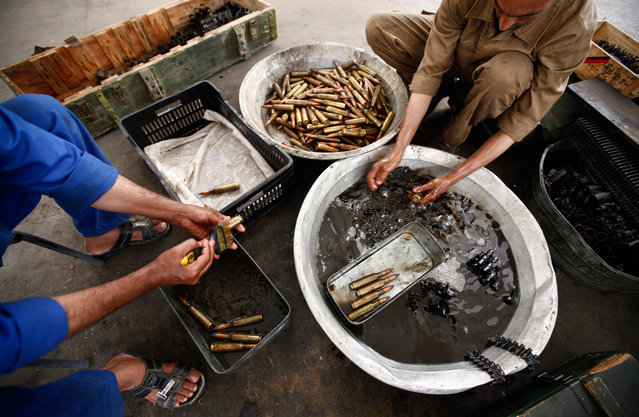 Libyans remove rust from ammunition in the western Libyan city of Misurata on June 7. (Photo by Zohra Bensemra/Reuters)