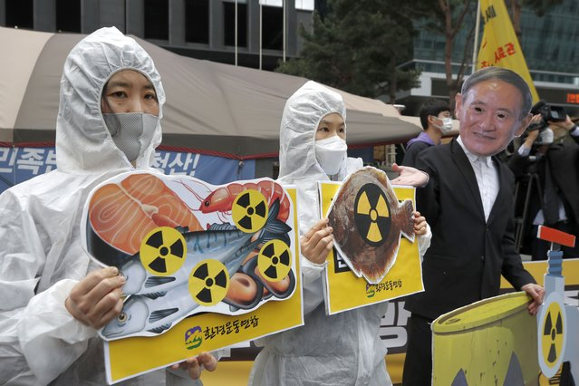 Environmental activists wearing a mask of Japanese Prime Minister Yoshihide Suga and protective suits perform to denounce the Japanese government's decision on Fukushima water, near the Japanese embassy in Seoul, South Korea, Tuesday, April 13, 2021. Japan's government decided Tuesday to start releasing massive amounts of treated radioactive water from the wrecked Fukushima nuclear plant into the Pacific Ocean in two years – an option fiercely opposed by local fishermen and residents. (Photo by Lee Jin-man/AP Photo)