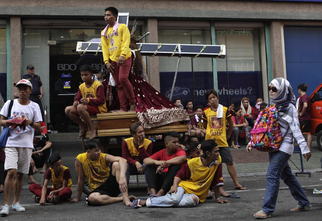 Devotees wait for the start of a procession of Black Nazarene replicas two days before the annual parade of the Black Nazarene in Manila, Philippines January 7, 2016. (Photo by Janis Alano/Reuters)