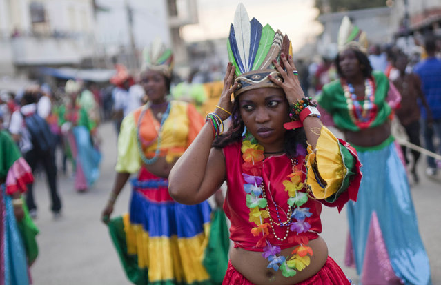 A dancer adjusts her crown during a Carnival parade to the national palace in Port-au-Prince, Haiti, Monday, February 16, 2015. (Photo by Dieu Nalio Chery/AP Photo)
