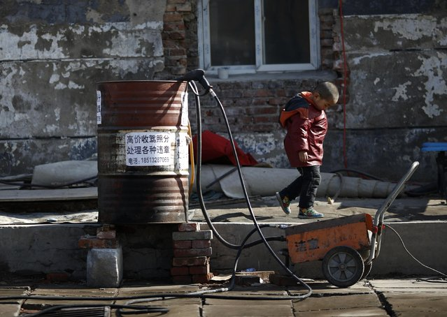 A boy walks past an oil barrel which is being used as a water bucket at a car wash in a migrant workers' village in Beijing February 12, 2015. (Photo by Kim Kyung-Hoon/Reuters)