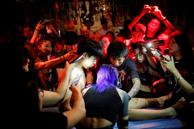 Spectators watch as professional body artist Wei Yilaien and her assistants prepare Viktor Liu for body suspension at a bar in Shanghai, China on September 16, 2018. (Photo by Aly Song/Reuters)