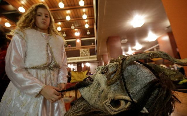 A girl dressed as an angel prepares a mask for a Krampus show, the traditional parade where people in costumes and masks perform an old ritual to disperse the ghosts of winter, in the southern Bohemian town of Kaplice, December 10, 2016. (Photo by David W. Cerny/Reuters)