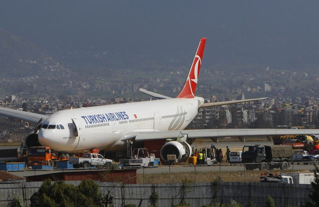 Workers try to remove a Turkish Airlines jet that skidded after landing at Tribhuwan International Airport in Kathmandu, Nepal, Friday, March 6, 2015. Nepal's only international airport will remain closed at least another day as workers attempt to remove a Turkish Airlines jet that skidded after landing Wednesday morning, blocking the single runway, aviation officials said Friday. (AP Photo/Niranjan Shrestha)