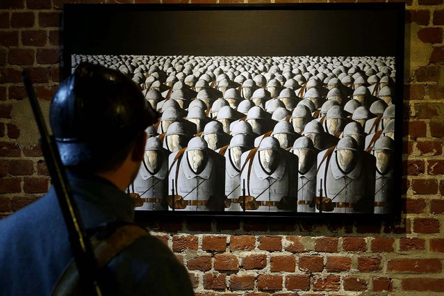 """A historical reenactor wearing a Poliu (French soldier in World War I) uniform looks at a contemporary painting by Sebastien Roche titled """"Les Sans-Visages"""" (Without Faces) during an exhibition about World War I at the fort of Seclin near Lille, France, on Oktober 13, 2013. (Photo by Pascal Rossignol/Reuters)"""