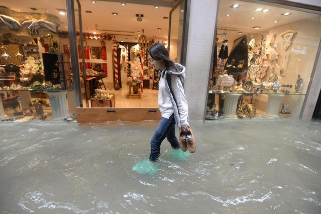 A woman walks in a flooded street of Venice, Italy, Monday, October 29, 2018, as, according to city officials, 70 percent of the lagoon city has been flooded by waters rising 149 centimeters (more than 58 1/2 inches) above sea level. Venice frequently floods when high winds push in water from the lagoon, but Monday's levels are exceptional and forecast to rise even higher, to 160 centimeters (nearly 63 inches) by mid-afternoon. (Photo by Andrea Merola/ANSA via AP Photo)