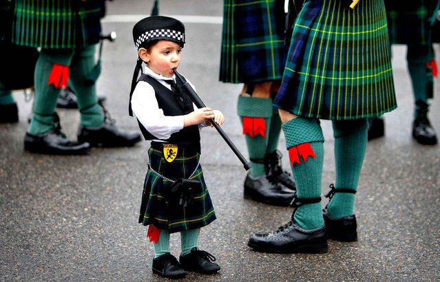 Rowan Miller, 2, stands next to his Grandfather Ian Seivwright as the Shelby County Sheriff's Pipe Band warms up before the start of the annual St Patrick's Day parade Saturday, March 14, 2015 in Memphis, Tenn. (Photo by Jim Weber/AP Photo/The Commercial Appeal)