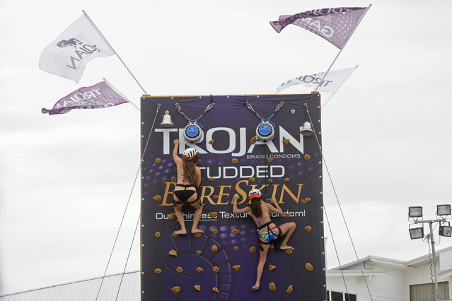 Party goers scale a climbing wall sponsored by Trojan condoms during spring break festivities in Panama City Beach, Florida March 13, 2015. (Photo by Michael Spooneybarger/Reuters)