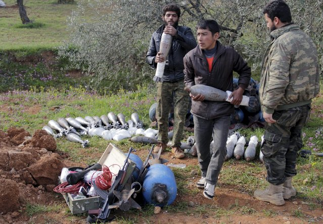 Rebel fighters from Suqour al-Sham Brigade carry mortar shells to be launched towards forces loyal to Syria's President Bashar Al-Assad in Idlib countryside March 19, 2015. (Photo by Mohamad Bayoush/Reuters)