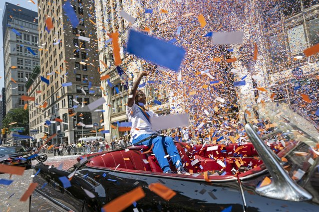 Grand marshal Sandra Lindsay, a health care worker who was the first person in the country to get a COVID-19 vaccine shot, waves to spectators as she leads marchers through the Financial District as confetti falls during a parade honoring essential workers for their efforts in getting New York City through the COVID-19 pandemic, Wednesday, July 7, 2021, in New York. The parade kicked off at Battery Park and travel up Broadway in lower Manhattan, the iconic stretch known as the Canyon of Heroes, which has hosted parades honoring world leaders, celebrities and winning sports teams. (Photo by John Minchillo/AP Photo)