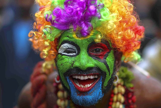 """A devotee of Hindu goddess Kali smeared in color performs a ritual during the """"Bonalu"""" festival at the Golconda Fort in Hyderabad, India, Sunday, July 11, 2021. Bonalu is a month-long Hindu folk festival of the Telangana region dedicated to Kali, the Hindu goddess of destruction. (Photo by Mahesh Kumar A./AP Photo)"""