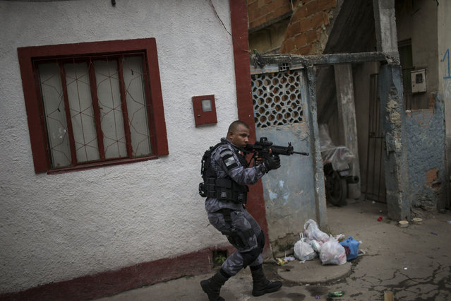 A military police officer patrols an alley at the Roquette Pinto shantytown, part of the Mare slum complex in Rio de Janeiro, Brazil, Wednesday, April 1, 2015. (Photo by Felipe Dana/AP Photo)