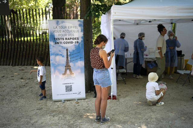 """A visitor registers for a covid-19 test at the Eiffel Tower in Paris, Wednesday, July 21, 2021. Visitors now need a special COVID pass to ride up the Eiffel Tower or visit French museums or movie theaters, the first step in a new campaign against what the government calls a """"stratospheric"""" rise in delta variant infections. (Photo by Daniel Cole/AP Photo)"""