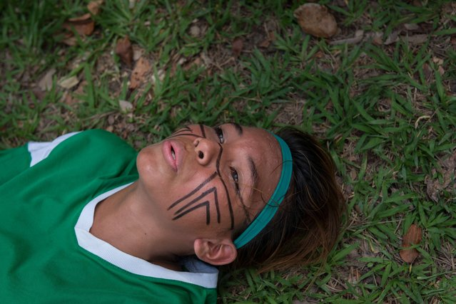 A female indigenous player takes a rest during the final match of Peladao, the amateur football tournament, in Manaus, Amazonas state, Brazil, on November 24, 2013. (Photo by Yasuyoshi Chiba/AFP Photo)