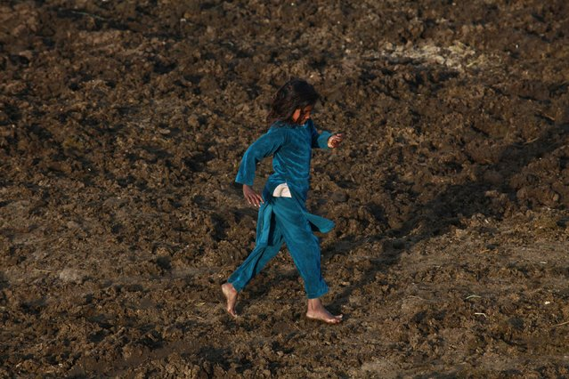 A girl runs barefoot on cows dung at a slum on outskirts of Lahore March 11, 2015. (Photo by Mohsin Raza/Reuters)