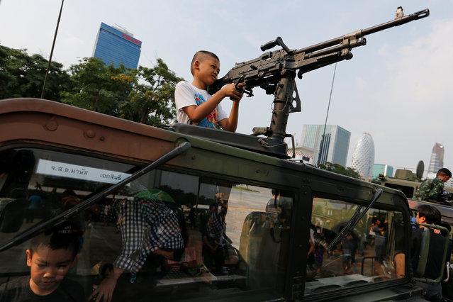 A boy plays with a weapon on the top of an army vehicle during Children's Day celebration at a military facility in Bangkok, Thailand January 14, 2017. (Photo by Jorge Silva/Reuters)