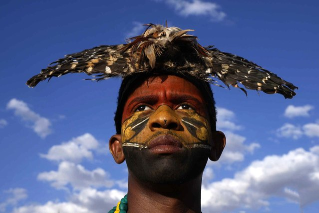 """A young Indigenous man with a traditional owl feather headdress looks on during the """"Luta pela Vida"""" or Struggle for Life camp, in front of the National Congress, in Brasilia, Brazil, Tuesday, August 24, 2021. Indigenous groups are in the capital for a weeklong Struggle for Life mobilization to protests against a Supreme Court ruling that could undermine rights to their lands, and against President Jair Bolsonaro's government. (Photo by Eraldo Peres/AP Photo)"""