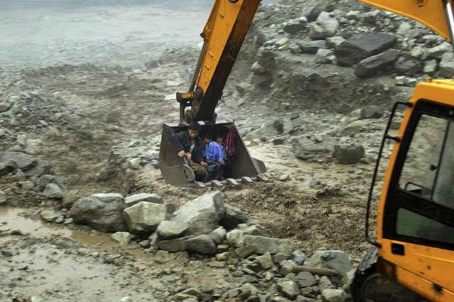 An excavator moves villagers away from a flooded area during heavy rainfall in Yingxiu, Wenchuan county, Sichuan province, July 10, 2013. (Photo by Reuters/Stringer)