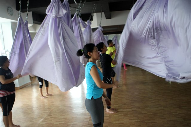 Some women wave the hammocks during the Anti-Gravity yoga class at Svarga e-Motion Sanctuary at Dharmawangsa Square, Jakarta, Saturday, April 18, 2015. (Photo by Jurnasyanto Sukarno/JG Photo)
