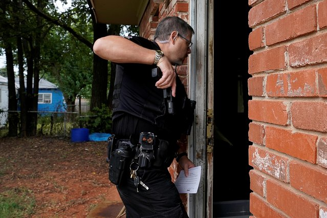 Oklahoma County Deputy Sheriff Brett Price enters a residence that the renters had already vacated during an eviction in Oklahoma City, Oklahoma, U.S. September 15, 2021. (Photo by Nick Oxford/Reuters)