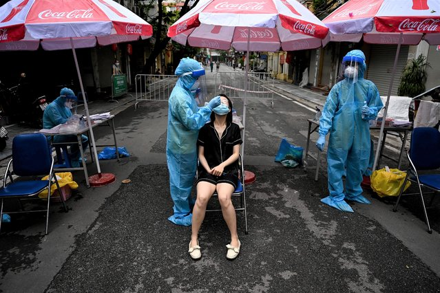 A health worker wearing personal protective equipment (PPE) collects swab samples from a woman (C) for Covid-19 coronavirus testing in the Old Quarter in Hanoi on August 11, 2021, amidst the government imposed two-week lockdown to stop the spread of the Covid-19 coronavirus. (Photo by Manan Vatsyayana/AFP Photo)
