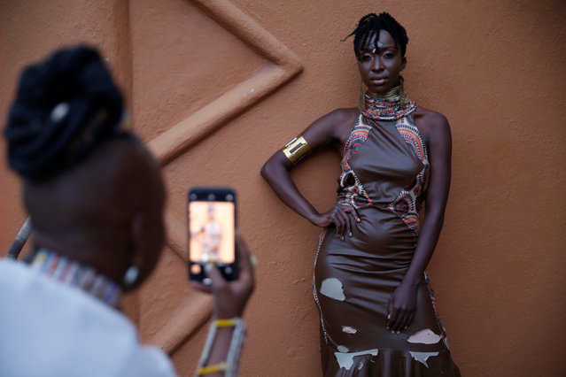 "A woman takes a picture of a model behind the scenes of a fashion show featuring African fashion and culture as part of a gala marking the launch of a book called ""African Twilight: The Vanishing Rituals and Ceremonies of the African Continent"" at the African Heritage House in Nairobi, Kenya on March 3, 2019. (Photo by Baz Ratner/Reuters)"