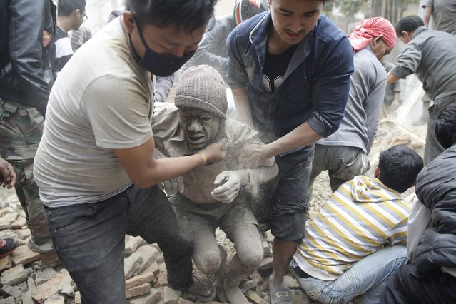 People free a man from the rubble of a destroyed building after an earthquake hit Nepal, in Kathmandu, Nepal, 25 April 2015. (Photo by Narendra Shrestha/EPA)
