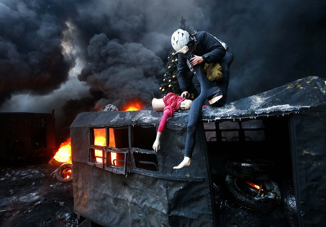 A protester breaks up a mannequin on the roof of a burned truck during clashes with police in Kiev, on January 23, 2014. (Photo by Sergei Grits/Associated Press)