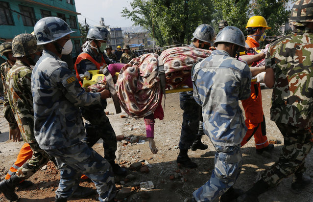 In this April 27, 2015 photo, rescue teams carry a body dug out of the collapsed Sitapyla church in Kathmandu, Nepal. (Photo by Wally Santana/AP Photo)