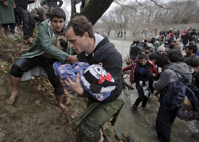 A man carries a baby as migrants cross a river, north of Idomeni, Greece, attempting to reach Macedonia on a route that would bypass the border fence, Monday, March 14, 2016. (Photo by Vadim Ghirda/AP Photo)