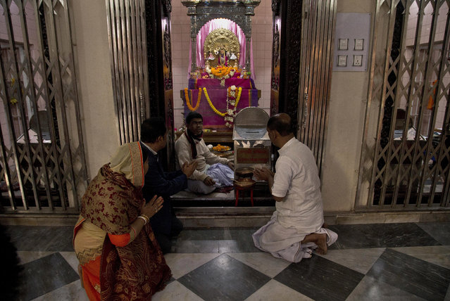 In this Tuesday, January 1, 2019 photo, Hindu devotees pray at the Dhakeshwari Temple in Dhaka, Bangladesh. While Sheikh Hasina is set to begin her third consecutive term as Bangladesh's prime minister following a landslide election victory, critics say having such an overwhelming majority in parliament could create space for her to become even more authoritarian. Still, Hasina enjoys a lot of support, especially from religious minorities in the Muslim-majority nation who say she has safeguarded their rights. At the Dhakeshwari Temple in Dhaka, Hindus poured in on Tuesday to pray and get a glimpse of the Goddess Durga, something they say was not possible under previous governments. (Photo by Anupam Nath/AP Photo)