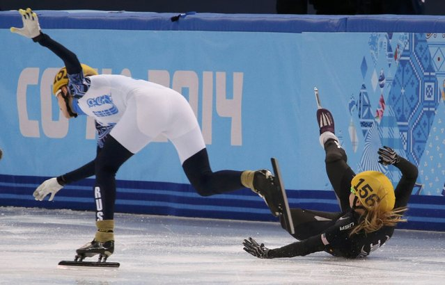 Russia's Valeriya Reznik (L) speeds past Jessica Smith (R) of the United States who crashes out while competing in the women's 500 metres short track speed skating heats event at the Iceberg Skating Palace during the 2014 Sochi Winter Olympics February 10, 2014. (Photo by David Gray/Reuters)