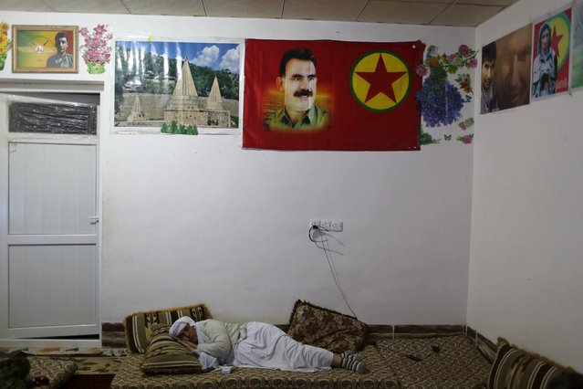 A displaced Yazidi woman takes a nap in a room at a base for female Kurdistan Workers Party (PKK) fighters in Sinjar, March 10, 2015. Hanging on the wall are pictures of jailed Kurdish militant leader Abdullah Ocalan (C), a Yazidi shrine and of PKK fighters who died in fighting. (Photo by Asmaa Waguih/Reuters)