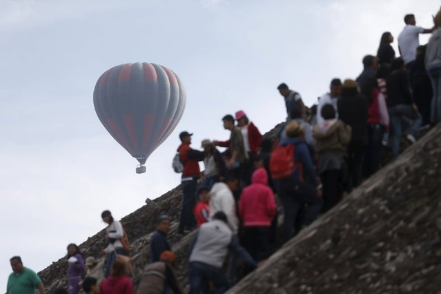 A hot air ball balloon floats past while people stand in line to climb the Pyramid of the Sun and welcome the spring equinox in the pre-hispanic city of Teotihuacan, on the outskirts of Mexico City, Mexico, March 20, 2016. Spring equinox in Teotihuacán is an annual event which takes place around the 20th and 21st of March at the pre-Hispanic site of Teotihuacán, Mexico. This event is mirrored by other similar events in other pre-Hispanic sites such as Chichén Itzá and Malinalco, Mexico State. (Photo by Edgard Garrido/Reuters)
