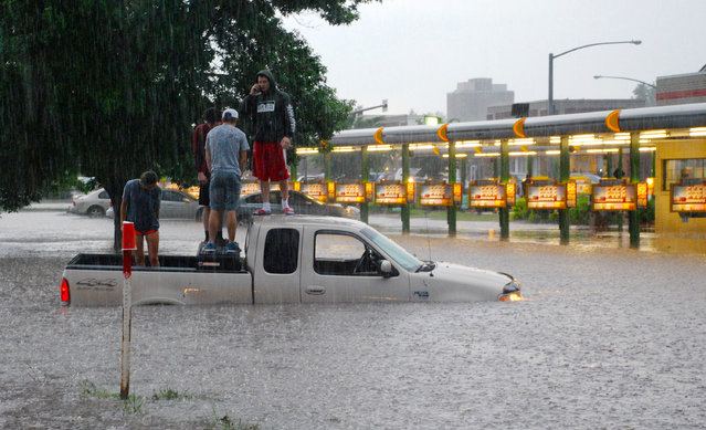 In this May 4, 2015 photo, people waiting for help stand on a truck caught in high water near a drive-in in Manhattan, Kan. A number of cars were stranded or nearly covered by flood waters Monday after heavy rain and thunderstorms hit Manhattan. (Photo by Megan Moser/AP Photo/The Mercury)