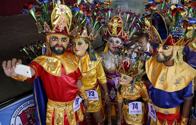 """A  family of penitents, dressed in masks and centurion costumes, known locally as """"Morions"""" take a picture during the start of Holy Week celebrations in Mogpog, Marinduque in central Philippines March 21, 2016. (Photo by Erik De Castro/Reuters)"""