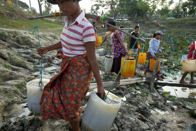 Local residents carry water in plastic containers as others line up to fetch water from a lake area Wednesday, May 6, 2015, in Dala Township, 15 kilometers (9 miles) south of Yangon, Myanmar. The water source is not good but invaluable for local residents. (Photo by Khin Maung Win/AP Photo)