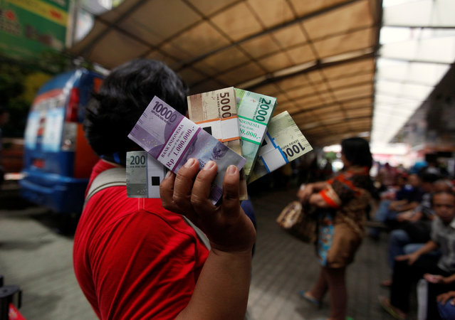A woman holds newly designed Indonesia Rupiah banknotes after exchanging her old bills at a Bank Indonesia mobile bank in Jakarta, Indonesia December 19, 2016. (Photo by Fatima El-Kareem/Reuters)