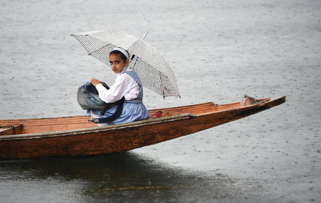 A Kashmiri schoolgirl sits on a boat on Dal Lake as she holds an umbrella during rainfall in Srinagar on April 24, 2019. (Photo by Tauseef Mustafa/AFP Photo)