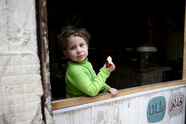 Aya, 4, eats bread as she stands in front of a shop in the rebel held Qaboun neighborhood of Damascus, Syria March 13, 2016. (Photo by Bassam Khabieh/Reuters)