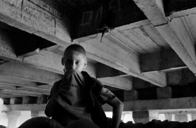 Denise Selivanov, 14, who has been living on the streets for four years inhales glue in his temporary home – a bridge overpass on a busy railway line, 2003. He considers himself lucky after escaping with four of his friends after an early morning police raid that netted 18 children that were living there. Denise, like many children, has spent time at the poorly equipped government shelters, but prefers life on the streets to the abusive he claims to have received there. (Photo by Kurt Vinion /Getty Images)