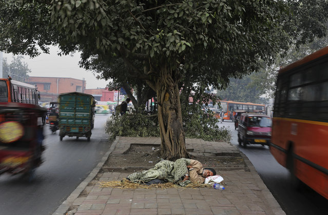 In this January 16, 2019, file photo, a homeless man sleeps on a median strip in New Delhi, India. In India, some 270 million people – nearly 22 percent of the country's population – live in poverty, making giveaways particularly attractive to voters. The Modi government in its interim budget in January announced farmers would be paid 6,000 rupees ($85) annually, benefiting as many as 120 million households and income tax relief to the middle class. (Photo by Altaf Qadri/AP Photo/File)