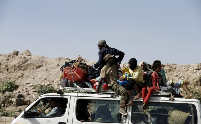 People ride atop a van as they flee their homes in an area where a rocket base was hit with air strikes in Yemen's capital Sanaa May 12, 2015. Saudi-led air strikes on a rocket base in the Yemeni capital Sanaa on Monday killed 90 people and wounded 300, a local official was quoted as telling the state news agency Saba. (Photo by Khaled Abdullah/Reuters)