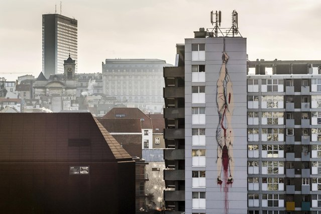 A mural of a gutted body hanging upside down with blood seeping out, is painted on an apartment building in Brussels on Thursday, January 26, 2017. (Photo by Geert Vanden Wijngaert/AP Photo)