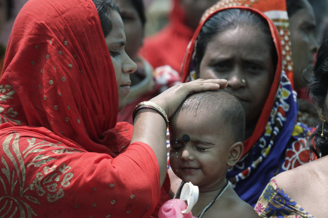 A woman wets the head of a child during an election rally addressed by Trinamool Congress leader and Chief Minister of West Bengal state Mamata Banerjee at Anchana in Mathurapur, about 60 kilometers south of Kolkata, India, Thursday, May 16, 2019. With 900 million of India's 1.3 billion people registered to vote, the Indian national election is the world's largest democratic exercise. The seventh and last phase of the elections will be held on Sunday. (Photo by Bikas Das/AP Photo)