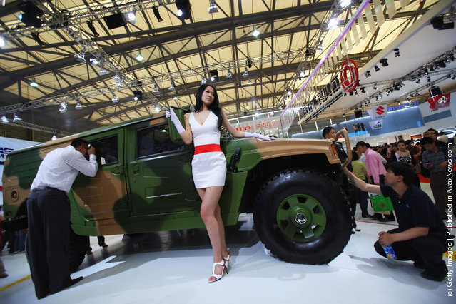 A model poses next to Dongfeng Motor's High Mobility Mutlpurposc Wheeled VehicleЈ HMMWVЈ
