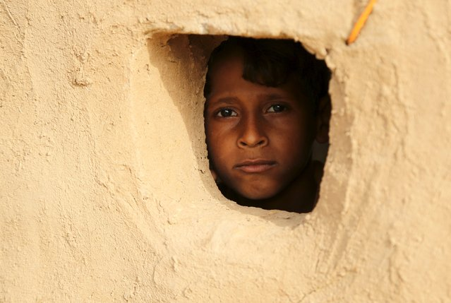 A boy looks from a window of his family's hut at the Shawqaba camp for internally displaced people who were forced to leave their villages by the war in Yemen's northwestern province of Hajjah March 12, 2016. (Photo by Abduljabbar Zeyad/Reuters)