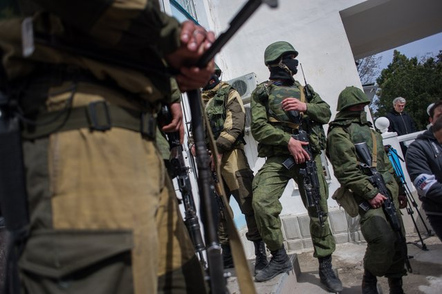 Soldiers in unmarked uniforms stand guard at the entrance to the Ukrainian navy headquarters stormed by Crimean pro-Russian self-defense forces in Sevastopol, March 19, 2014. (Photo by Andrew Lubimov/AP Photo)